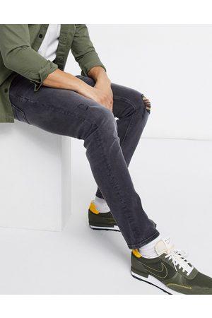ASOS Jean slim stretch effet usé avec déchirures aux genoux - délavé