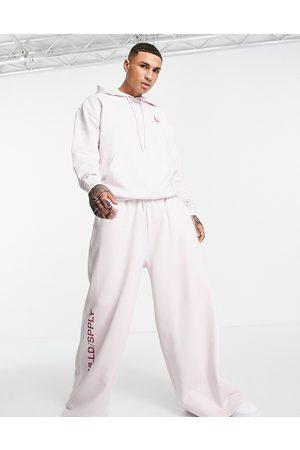 ASOS ASOS - Unrvlld Supply - Jogger ultra oversize à coutures apparentes et logo imprimé sur la jambe (pièce d'ensemble) - Lilas